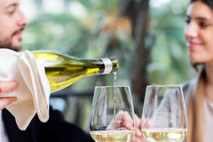 White wine pouring with couple in background. stock photography
