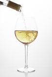 White wine pouring in a glass. From a bottle royalty free stock photos