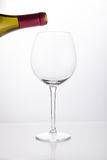 White wine pouring in a glass from bottle Stock Photography