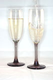 White wine pouring in glasses. Two tall flute glasses with white wine pouring in Royalty Free Stock Image