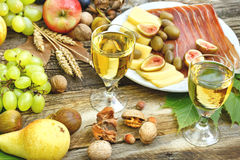 White wine, prosciutto, cheese and seasonal fruits on rustic table Stock Photos