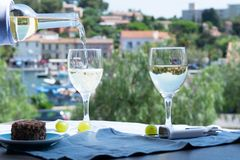 White wine of Provence, France, served cold with soft goat cheese on outdoor terrace in two wine glasses. In sunny day royalty free stock photos