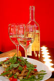 White wine with salad. White wine at restaurant with salad on a red background Royalty Free Stock Image