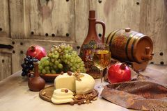 The white wine served with cheese and fruit. White wine, cheese, nuts, grapes and pomegranate Royalty Free Stock Photos