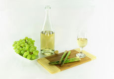 White wine and sides. Picture of Still life - bottle and glass with white wine and sides grapes over the dish and asparagus over wooden cutting board over white Stock Photo