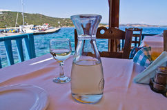 White wine on a table in a shade of a typical greek taverna by the sea. Drinking white wine in a shade of a typical greek taverna by the sea, Amoulani island stock photography