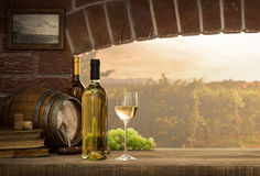White wine tasting in the cellar. White wine tasting in the wine cellar: wineglass and bottles next to the window and panoramic view of vineyards at sunset stock photo