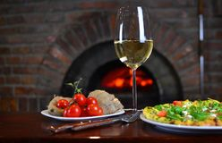 White wine in a wineglass and pizza. Wine in a wineglass with a pizza and cherry tomatoes near the old fireplace in a authentic restaurant Stock Photography