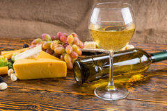 White Wine on Wood Table with Cheeses and Grapes Stock Images