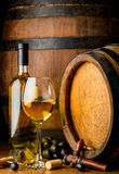 White wine on wooden barrel background. Wine bottle and glass, cheese and grapes in still life on wooden barrel background stock photos