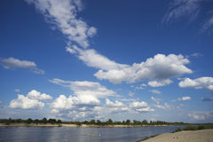 White-winged clouds on  sky and two kayaks float away into distance in the river. Royalty Free Stock Photo