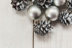 White winter cones on the wooden table with silver balls.Christmas composition stock image
