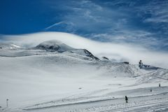 White winter mountains covered with snow in blue cloudy sky. Mountain skiers ride the slope. Alps. Austria. Pitztaler Gletscher royalty free stock images