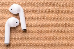 White wireless headphones on a beautiful wicker napkin. Wireless headphones in white on a beautiful wicker napkin, the concept of youth and cheerful mood royalty free stock photography