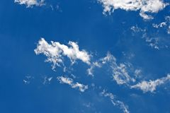 WHITE WISPS OF CLOUD AGAINST BLUE SKY Stock Photos
