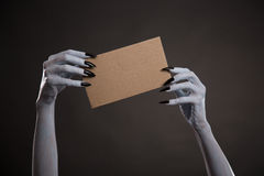 White witch hands with black nails holding blank cardboard Stock Images