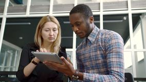 White woman and African American man look closely at tablet on hands. stock video