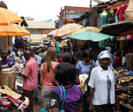White Woman in African Market Shopping. KAMPALA, UGANDA - SEPTEMBER 28, 2012.  A white woman walks away through a market shopping among locals in Kampala, Uganda Royalty Free Stock Photography