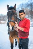 White woman and Arab man next to horse in winter, international couple royalty free stock photography