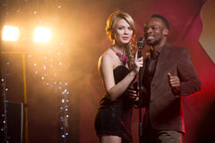 White woman and black man singing into a microphone at the bar, couple singing Royalty Free Stock Image