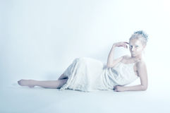 White woman posing alone in white room Royalty Free Stock Photography