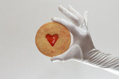 White woman's gloves holding a cookie with heart-shaped jam isolated on white background. White elegant female gloves holding a cookie with heart-shaped lam Stock Photography