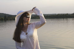 White woman in sun hat posture on beach lake. Summer day Stock Photography