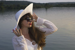 White woman in sun hat posture on beach lake. Summer day Stock Image