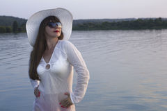 White woman in sun hat posture on beach lake. Summer day Royalty Free Stock Image
