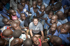 White woman surrounded by African children. A white woman meets a group of friendly African children in Uganda. The children are happy and smiling Stock Photo