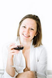 White woman in white shirt drinks red wine. White young smiling woman with light brown hair in a white shirt with a glass of red wine in her jand on white Stock Photos