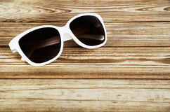 White woman& x27;s sunglasses close-up on a wooden background Stock Images