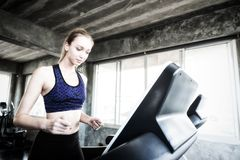 White women are exercising on exercise machines. Young people running on treadmill in gym. Young caucasian exercising on a royalty free stock photos