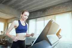 White women are exercising on exercise machines. Young people running on treadmill in gym. Young caucasian exercising on a stock images