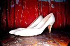 White Women's Shoes on Red Background Stock Photo