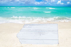 White wood board on the sandy beach. Empty white wood board on the sandy beach near the ocean Royalty Free Stock Photo