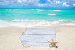 White wood board with starfish on the sandy beach Royalty Free Stock Images
