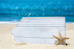 White wood board with starfish on the sandy beach Stock Photography