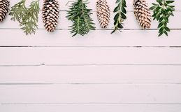 White wood Christmas border with snow covered pinecones. stock photo
