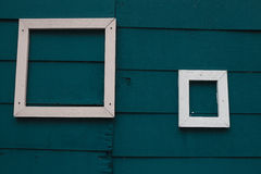 2 white wood frame on green wall Stock Images