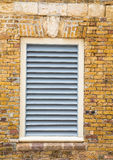 White Wood Shutters in Old Brick Wall Stock Image