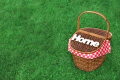 White Wood Sign Home On The Picnic Basket. Bright Summer Green Grass In The Background Royalty Free Stock Photos