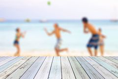 White wood table on blurred young tourists playing ball on beach royalty free stock photography