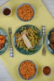 Flat lay overhead view of a table laid with Chinese rice and meat dishes. A white wood table with yellow cloth and green dishes with Chinese food. Including rice Royalty Free Stock Photography