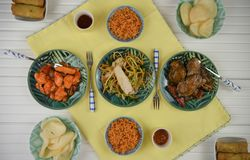 Flat lay overhead view of a table laid with Chinese food meat dishes. A white wood table with yellow cloth and green dishes with Chinese food. Including rice Royalty Free Stock Photo