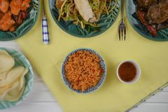 Flat lay overhead view of a table laid with Chinese food dishes. A white wood table with yellow cloth and green dishes with Chinese food. Including rice prawn Royalty Free Stock Photo
