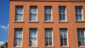 Windows in Old Red Stucco Building Royalty Free Stock Images