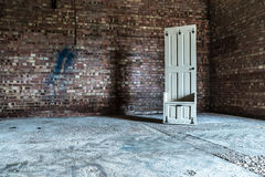 White Wooden 6 Panel Board Rack Behind Brown and White Concrete Bricks Wall on Gray Flooring Stock Photo