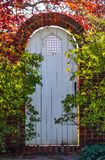 White wooden arched garden gate in autumn in brick wall surrounded by foliage with the sunlight shining around it and through colo stock images