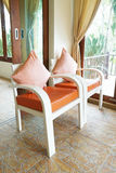 White wooden armchairs with orange pillow Royalty Free Stock Images